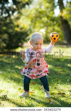 Happy child is outside in the park. She is walking and playing with her ball.