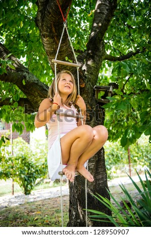 Happy child is playing on rope ladder outside in nature