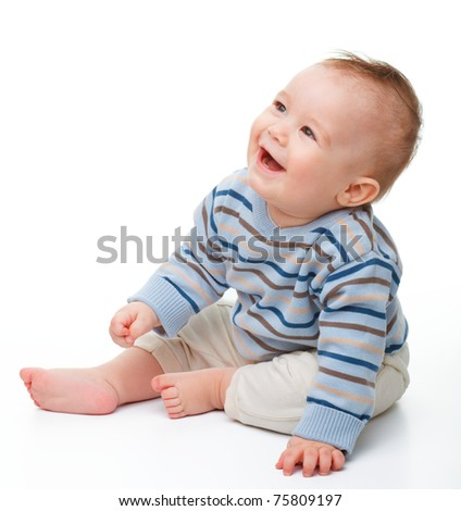 Happy child is sitting on floor, isolated over white