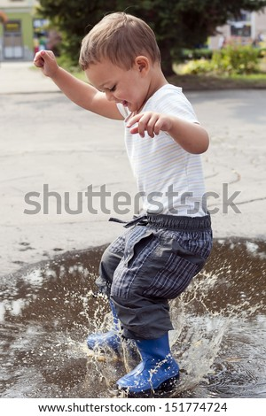 Happy child jumping into a street puddle. - stock photo