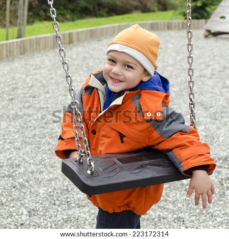 Happy child leaning a swing in a children playground. - stock photo