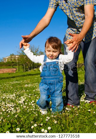Happy child learning to walk - stock photo