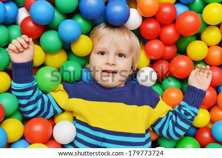 Happy child lies at colorful plastic balls