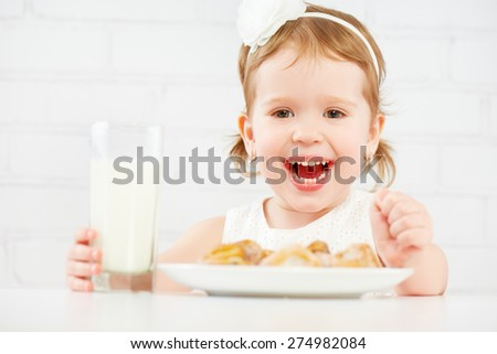 happy child little girl eats cookies and milk - stock photo