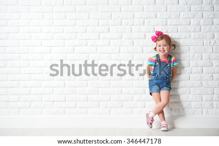 Happy child little girl laughing at a blank empty brick wall - stock photo