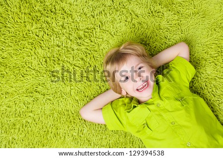 Happy child lying on the green carpet background. Boy smiling and looking at camera