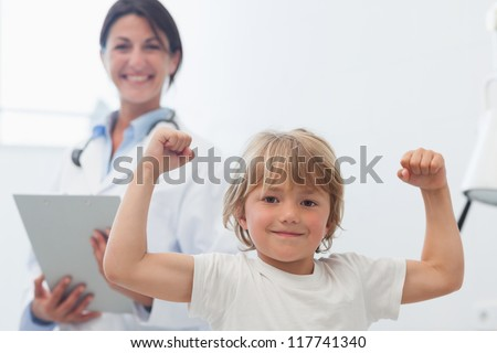 Happy child next to a doctor in hospital ward - stock photo
