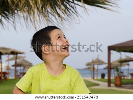 Happy child on a beach with umbrellas in tourist holiday resort.  - stock photo