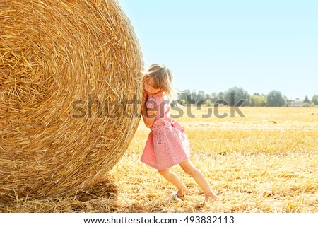 happy child on a field with bales harvest in autumn