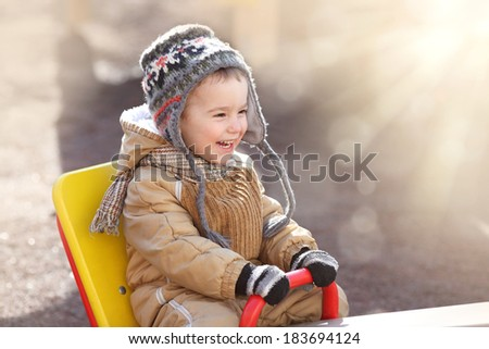 happy child on a swing on a sunny spring day - stock photo