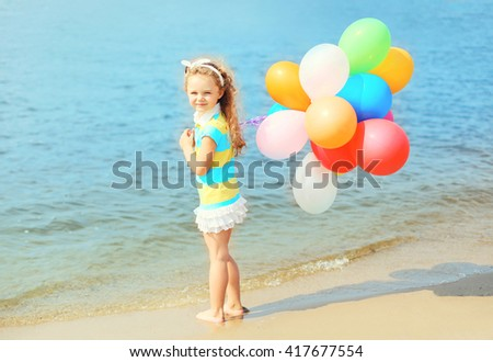 Happy child on beach with colorful balloons near sea summer  - stock photo