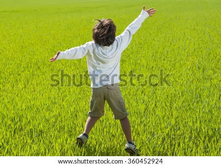 Happy child on beautiful green yellow grass field - stock photo