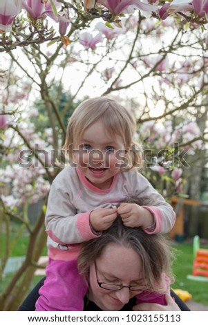 happy child  on mothers shoulder with some magnolia tree leaves in her hand