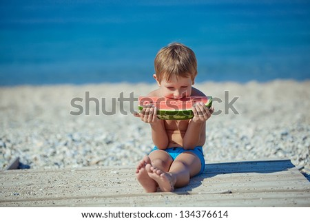 Happy child on the sea with watermelon - stock photo