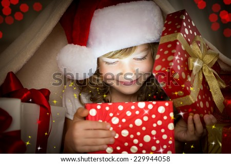 Happy child opening Christmas gift box. Funny baby dressed in Santa Claus hat in bedroom. Portrait of smiling kid at home. Xmas holiday concept - stock photo