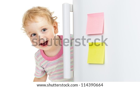 happy child or boy hiding behind fridge door - stock photo