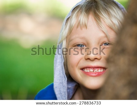 Happy child peeking from behind a tree with copy-space