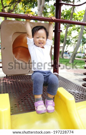 Happy child play on slide playground area in the park, asian - stock photo