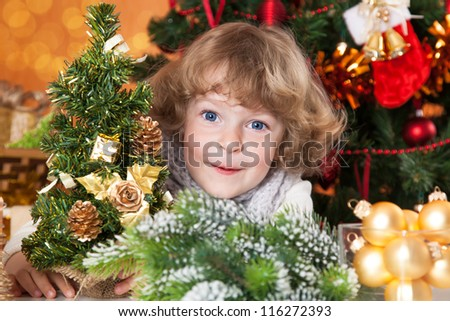 Happy child playing against Christmas tree with decorations