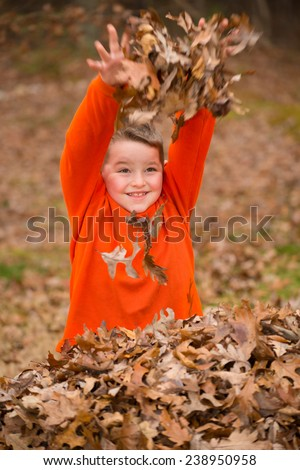 Happy child playing in a leaf pile during fall or winter - stock photo