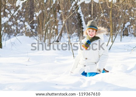 Happy child playing in a snow field on a sunny winter day