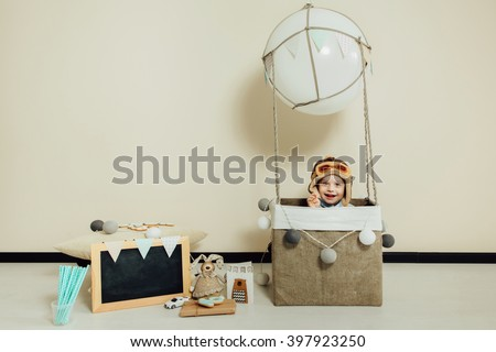 Happy child playing in basket of air balloon. Kid having fun at home. Young pilot indoors at solid color background with copy space. Boy in hat like a helmet looking at camera. Blank chalkboard. - stock photo