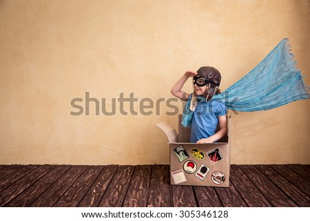 Happy child playing in cardboard box. Kid having fun at home - stock photo
