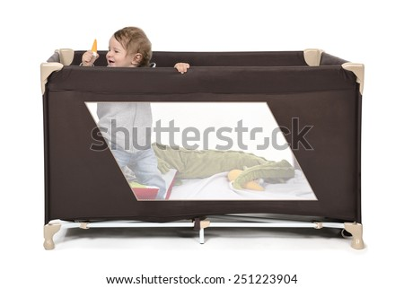 Happy child playing in his portacrib bed