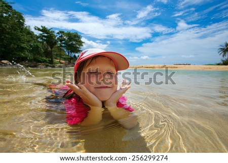Happy child playing in sea. Summer vacations concept - stock photo