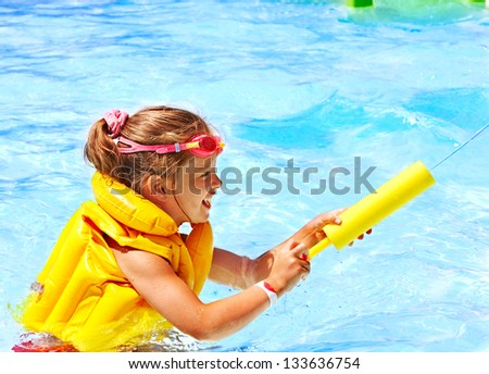 Happy child playing in swimming pool. - stock photo