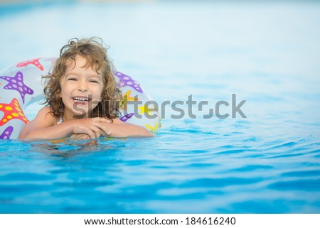 Happy child playing in swimming pool. Summer vacations concept - stock photo