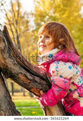 Happy child playing in the park climbing on the tree - stock photo