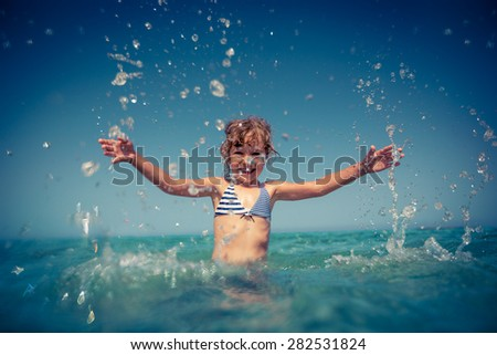 Happy child playing in the sea. Summer vacation concept - stock photo