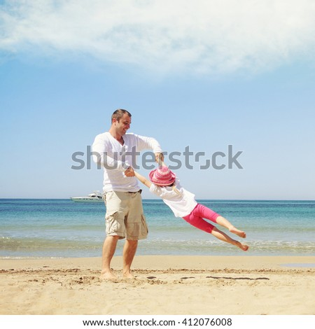Happy child playing iwith her father. Summer vacation concept - stock photo
