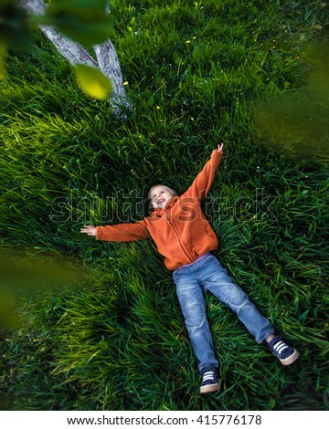 Happy child playing on grass - stock photo
