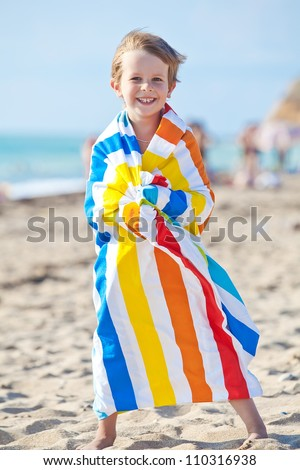 Happy child playing on the beach in summer - stock photo