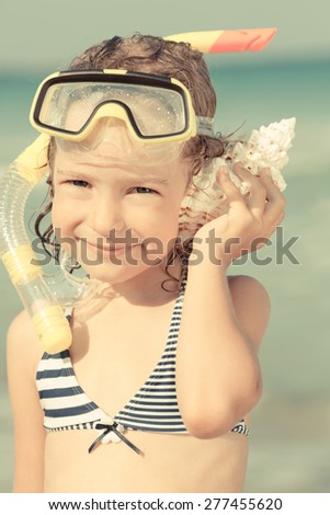 Happy child playing on the beach. Kid listen seashell. Summer vacations concept. Retro toned image - stock photo