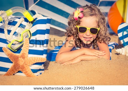 Happy child playing on the beach. Kid lying on sand. Summer vacations concept - stock photo