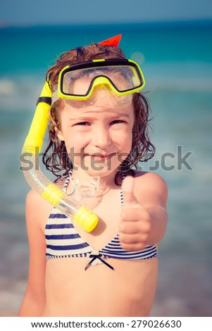 Happy child playing on the beach. Kid showing thumbs up. Summer vacations concept - stock photo