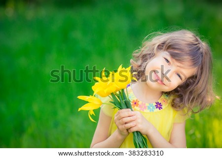Happy child playing outdoors in spring park - stock photo