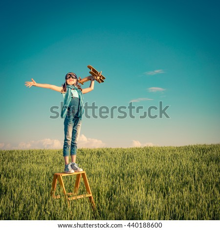 Happy child playing outdoors. Kid having fun in summer field. Child with toy airplane. Kid pretend to be pilot. Travel, vacation and freedom concept. Childhood, imagination, dream