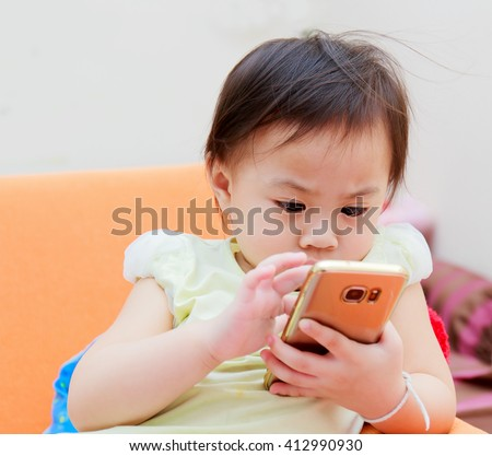 happy child  playing phone on sofa - stock photo