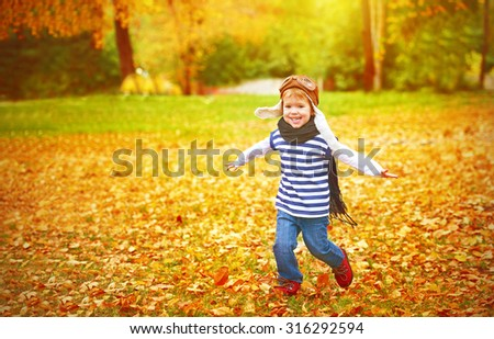 happy child playing pilot aviator and dreams outdoors in autumn - stock photo