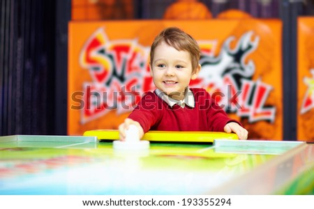 happy child playing table air hockey - stock photo