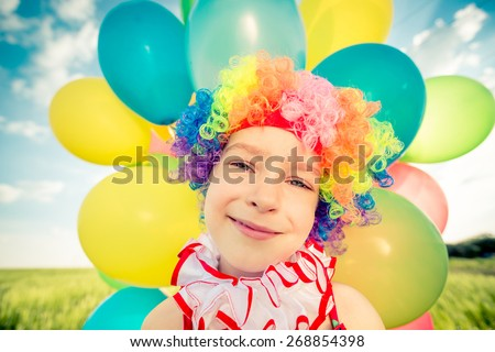 Happy child playing with colorful toy balloons outdoors. Smiling kid having fun in green spring field against blue sky background. Freedom concept