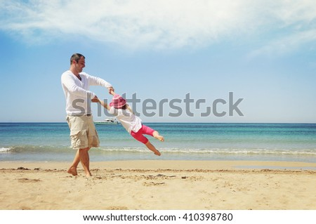 Happy child playing with her father. Summer vacation concept - stock photo