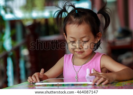 Happy child playing with her tablet outdoors on the table during relax time.