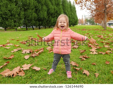Happy child playing with leaves in park