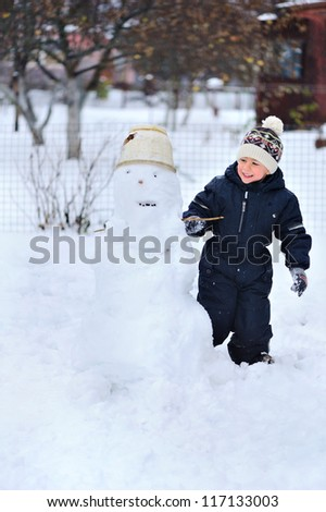 Happy child playing with snow and sculpts snowman.