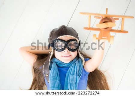 Happy child playing with toy airplane. Kid lying on wooden floor at home - stock photo